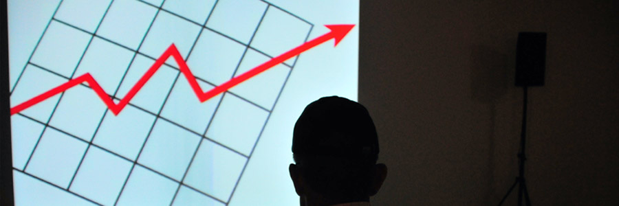 The Hidden Benefits Of Sustainability To The Bottom Line Man In Front of Graph